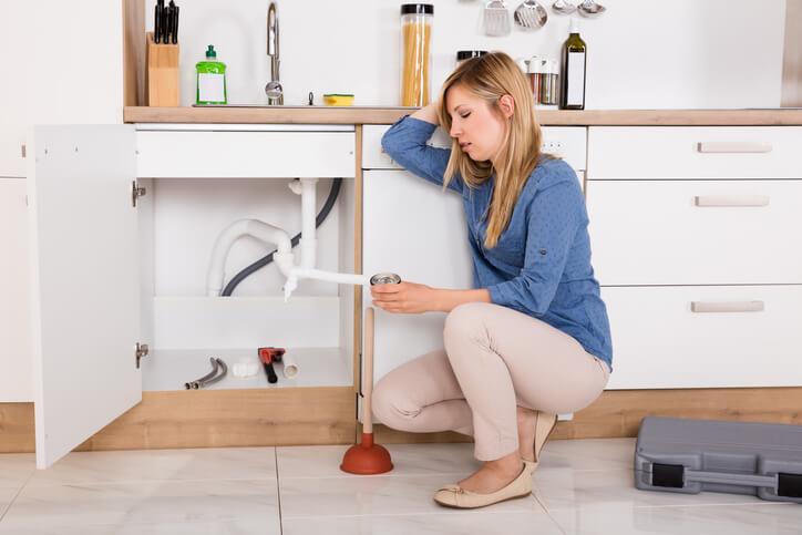 Woman Trying To Fix Plumbing