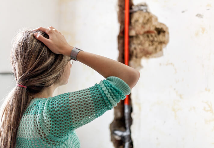 Woman Looking A Burst Pipe